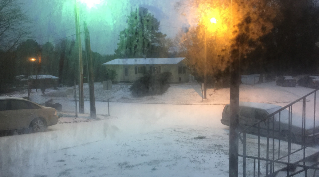 picture of icy snow with two different color street lamps